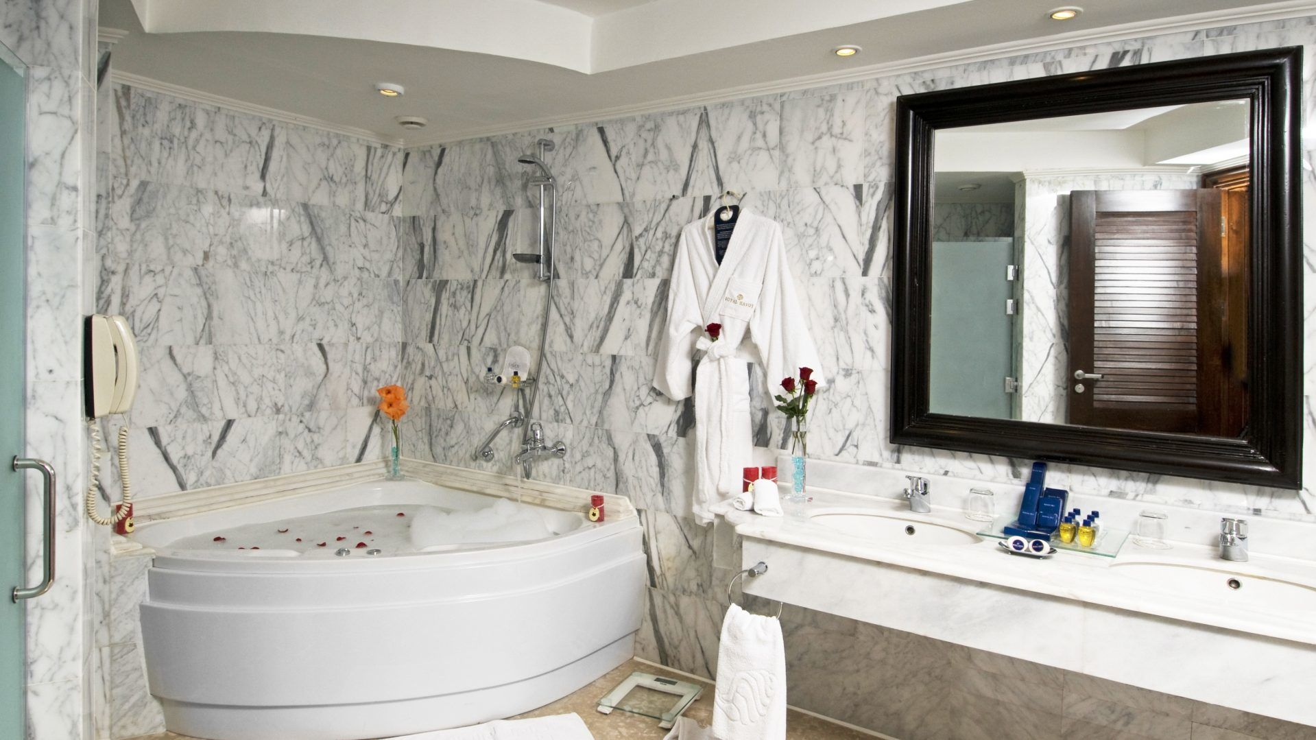 A Bedroom With A White Tub Sitting Next To A Sink