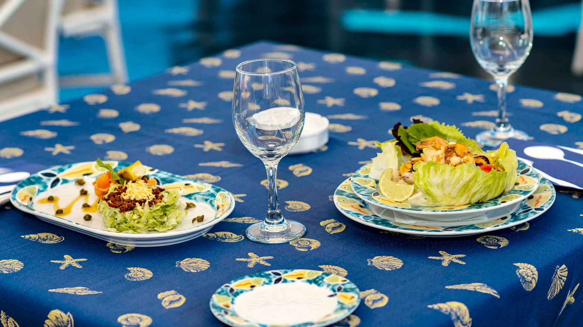 A Blue And White Plate Sitting On Top Of A Table With Wine Glasses